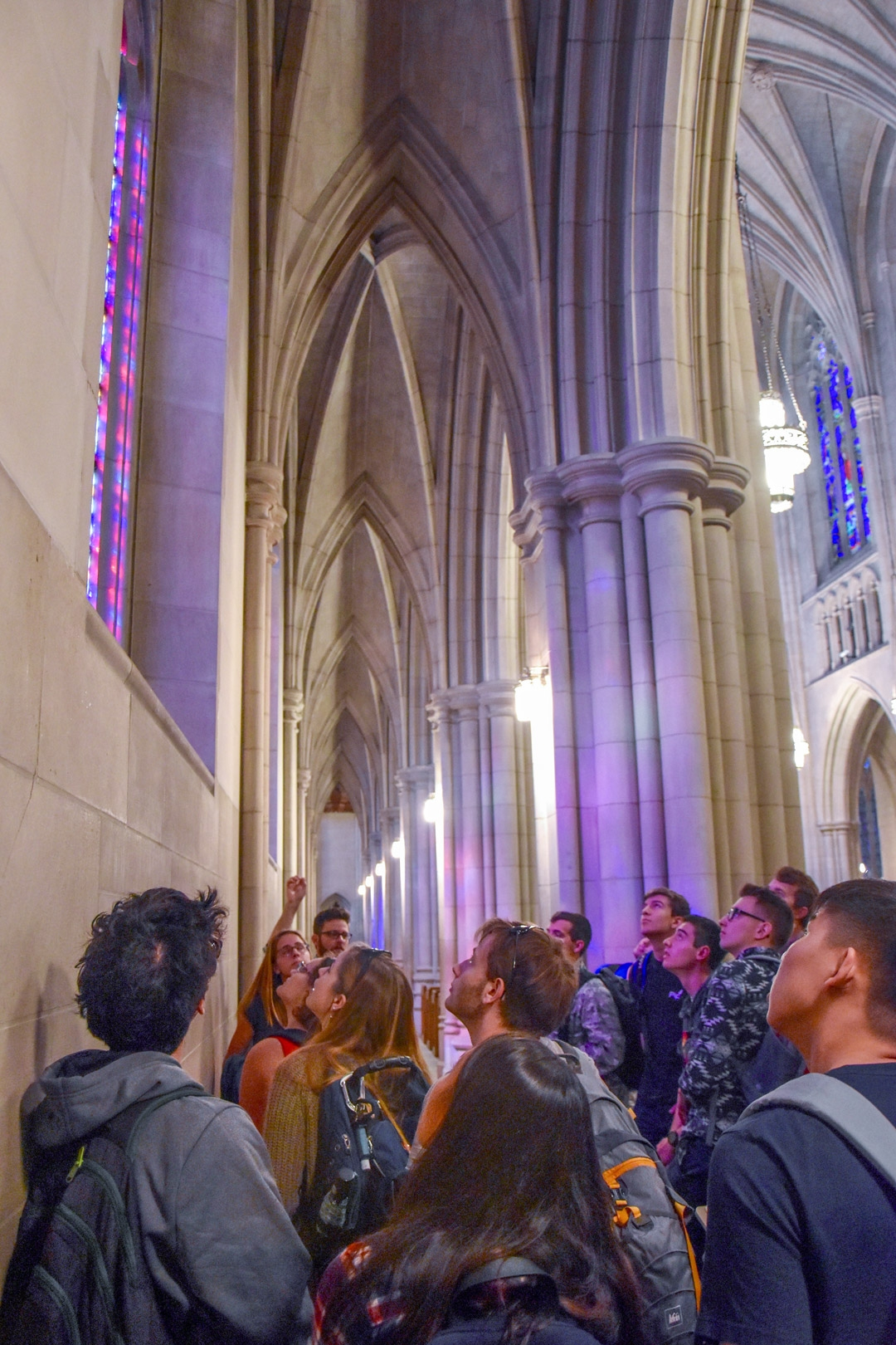 A group looking at a stained glass window