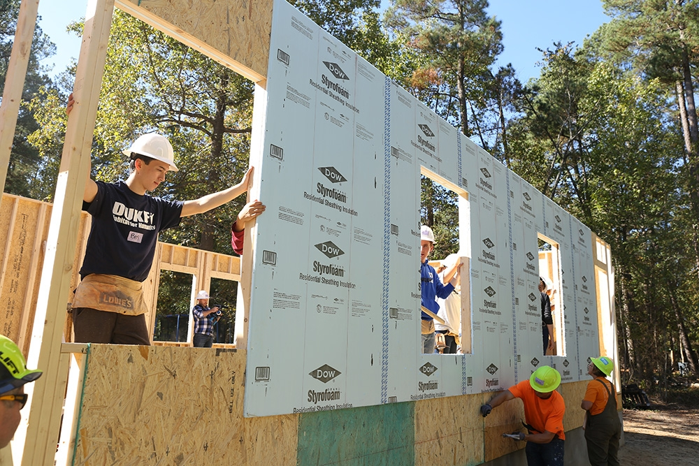 Duke students and community volunteers raise a wall on a Habitat for Humanity house